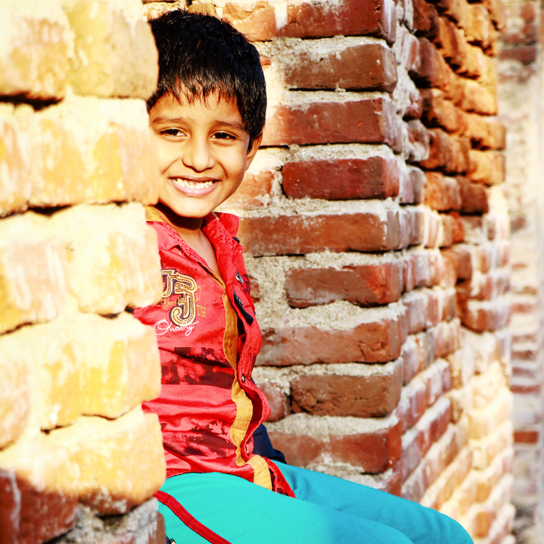 Indian kid Sitting on Wall Free Images